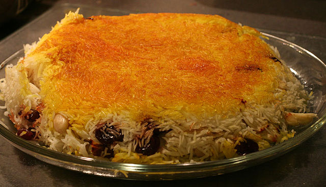 Rice dish on platter with browned rice on the top and almonds and cherries emerging from edges.