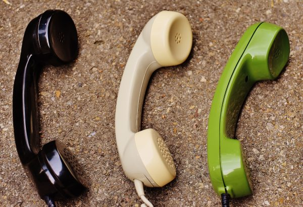 Three telephone receiver models, one each color black, yellow, and green, on sandy surface.