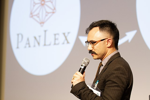 Speaker Ben Yang in front of slide displaying PanLex logo.