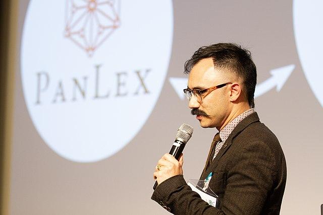 Speaker Ben Yang in front of slide displaying PanLex logo.